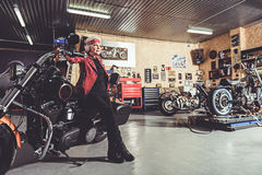 Outgoing pensioner bracing on bike in garage Stock Photography