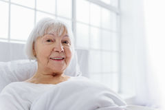 Outgoing pensioner reclining in comfortable cot Royalty Free Stock Photography