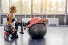 Outgoing retiree doing exercises on fitball. Cheerful coach training smiling grandmother. Happy granny engaging fitness in workout room Royalty Free Stock Photos