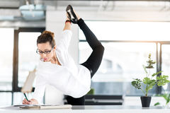Outgoing secretary doing gymnastic exercise in office Royalty Free Stock Photos
