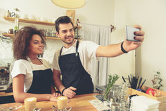 Outgoing waiters making photo on mobile phone. Cheerful women and positive men taking selfie on mobile phone while standing at bar counter. Two cups of latte are Stock Image