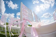 Tapes fly in the wind. Romantic wedding ceremony. White wooden chairs with ribbon and flowers on a green lawn. Nice. Outgoing wedding ceremony. Decor Studio Stock Photo
