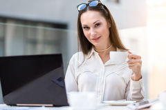 Outgoing woman drinking cup of delicious coffee. Portrait of happy lady tasting mug of hot beverage while working at laptop in cafe. She sitting at desk and Royalty Free Stock Images