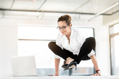 Outgoing woman having awkwarded pose in office. I cannot sit comfortably. Female demonstrating happiness while working with laptop in lotus position. Uncomfort Royalty Free Stock Photo