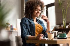 Outgoing woman hearing song in cafe Stock Photos