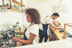 Outgoing woman making cup of beverage in cafe stock images