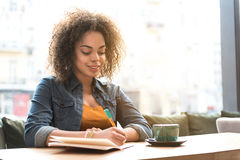 Outgoing woman making notes in scribbling-diary Stock Photos