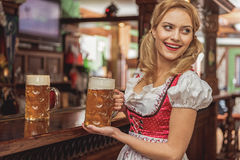 Outgoing woman serving glasses of beer Stock Photography