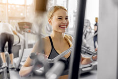 Outgoing woman training with pulldown station. Cheerful young female making exercise on triceps in fitness center. Sport concept Royalty Free Stock Photography