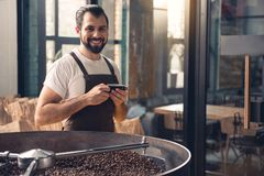 Outgoing worker drinking cup of beverage. Portrait of happy unshaven man having rest with appetizing mug of liquid while standing near coffee roaster machine Stock Photography