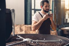 Outgoing worker tasting mug of liquid. Portrait of cheerful professional bearded coffee roaster drinking delicious hot beverage near appliance during break Royalty Free Stock Photos