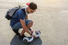 Outgoing young man walking with gyroscooter Royalty Free Stock Photos