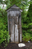 The Outhouse. Wooden Decorative Garden Outhouse with Moon Eclipse on Door Royalty Free Stock Photo