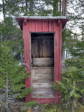 Outhouse. With missing door standing in the middel of a forest Stock Photos