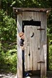 Outhouse con la donna che dà una occhiata fuori Immagini Stock