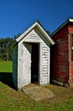 Outhouse Door Left Open. A rural white outhouse in excellent condition hand an open door stands next to a red shed Royalty Free Stock Photos