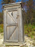 Outhouse with a little solar panel. Outhouse in Maine with a solar panel that charges the light inside stock images