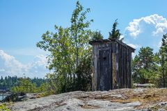 Outhouse, outdoor toilet on a cliff in archipelago landscape royalty free stock image