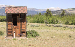 Outhouse on ranch. Old toilet with a mountain view on a ranch in America with copyspace Royalty Free Stock Image