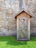 Outhouse rustico davanti alla parete di pietra dell'annata Immagini Stock
