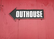Outhouse sign with arrow on a red wooden wall Royalty Free Stock Photos
