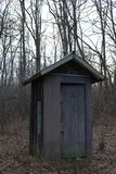 Outhouse in twilight amongst trees royalty free stock image