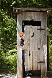 Outhouse with woman peeking out Stock Images