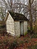 Outhouse in the Woods. An old rickety outhouse stands upright in the autumn treeless woods Royalty Free Stock Photography