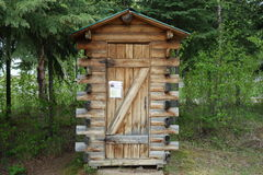 An outhouse in the woods. Stock Images