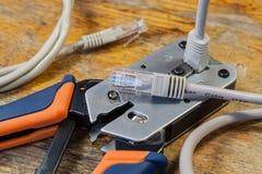 Outil à sertir pour le montage des connecteurs RJ45 sur le bureau dans un atelier Image stock