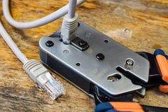 Outil à sertir pour le montage des connecteurs RJ45 sur le bureau dans un atelier Image libre de droits