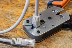 Outil à sertir pour le montage des connecteurs RJ45 sur le bureau dans un atelier Photo stock