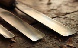 Outil de burin en bois de charpentier avec les copeaux lâches sur le vieil établi en bois superficiel par les agents Image stock