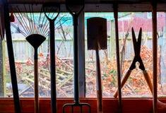 Outil de jardin accrochant dans une fenêtre de hangar Photographie stock