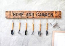 Outil de jardin accrochant sur le mur en béton avec le label en bois photo libre de droits