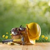 Outil et casque de construction sur le fond vert de nature Photographie stock