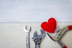 Outil et coeur rouge sur le tissu de toile avec l'espace sur le fond en bois blanc Photo libre de droits