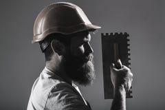 Outil, truelle, bricoleur, constructeur d'homme Outils de maçon, constructeur Travailleur barbu d'homme, barbe, casque de bâtimen photo stock