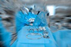 Outils chirurgicaux dans la salle d'opération avec les silhouettes brouillées de Image stock