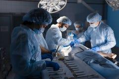 Outils chirurgicaux se trouvant sur la table avec l'infirmière près et les chirurgiens au fond photo libre de droits