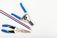 Outils d'électricien avec des accessoires, à dénuder de pince, fond blanc image stock