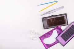 Outils d'extension de cil sur le fond blanc Accessoires pour des prolongements de cil Mèches artificielles Vue supérieure image stock