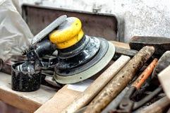Outils dans le garage, le marteau, le tournevis et la machine d'amortissement de puissance Photo stock