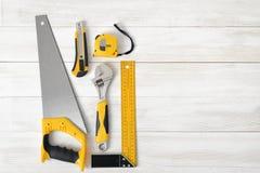 Outils de bâtiment comprenant la règle, la clé et le coupeur de centimètre placés dans le côté gauche sur la surface en bois avec Images stock