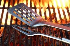 Outils de BBQ sur le gril chaud Photographie stock libre de droits