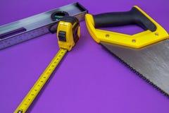 Outils de bricolage scie en bois jaune, agrafeuse, ruban métrique photographie stock libre de droits