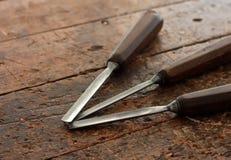 Outils de burin en bois de charpentier sur le vieil établi superficiel par les agents Photographie stock