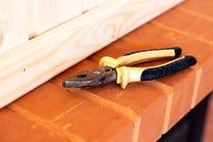 Outils de construction Pinces et burin sur la brique rouge photo libre de droits
