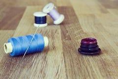 Outils de couture de vintage sur le fond en bois : bobines, aiguille, boutons Composition horizontale Image modifiée la tonalité photo libre de droits