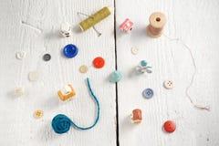 Outils de couture sur le fond en bois blanc Images stock